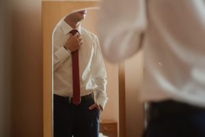 business man facing mirror with red tie