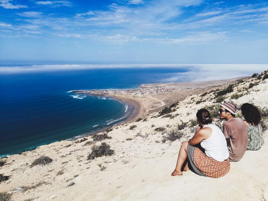three friends sit on beach looking at ocean