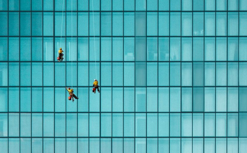 window cleaners suspended by blue building