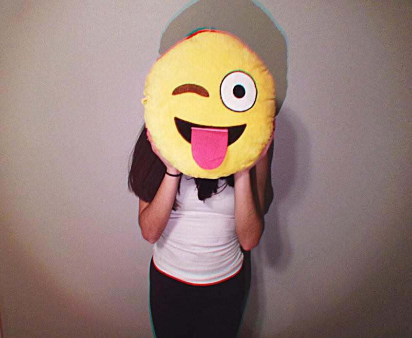 Person holding a smiley pillow